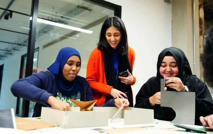 Three women making a prototype building on a table.