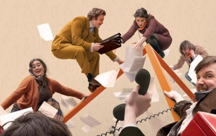 A crowd of 1970s workers chase paperwork on an orange cube