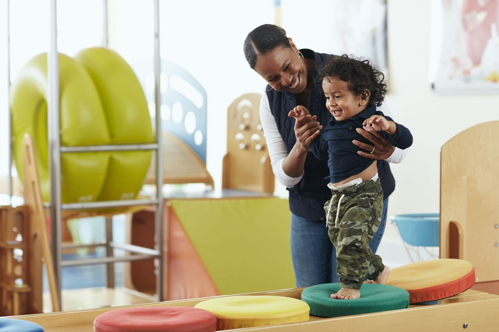 mother holding child on beam at Gymboree