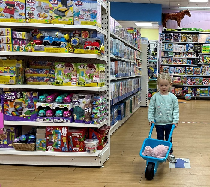 A young girl with a toy wheelbarrow walking in a toy shop.