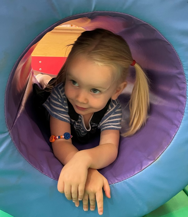 A young girl crawling through play centre equipment,