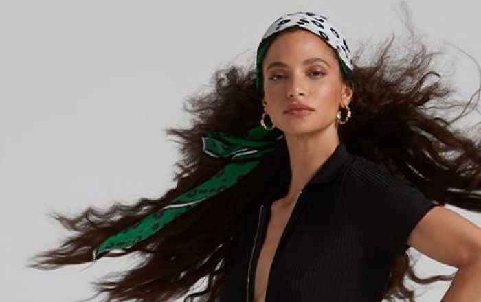 A woman wearing a headscarf and her hair blows in the wind.