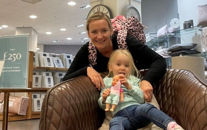 A woman and her daughter sitting on a chair in a shop.