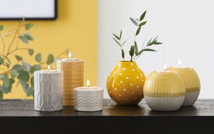 5 different yellow and white candles on a table.