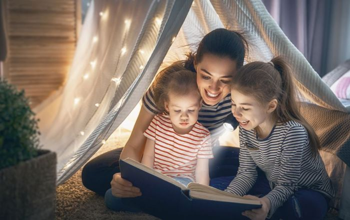 Two children and a parent reading a book under a blanket.