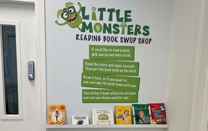 Little Monsters Reading Book Swop Shop logo on the wall and books on a shelf