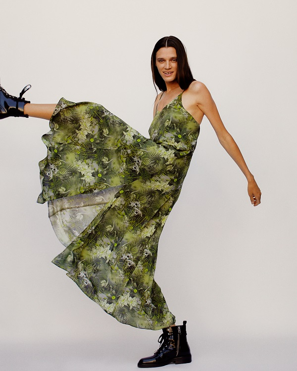A woman wearing a green floral dress from AllSaints she is kicking her leg up.