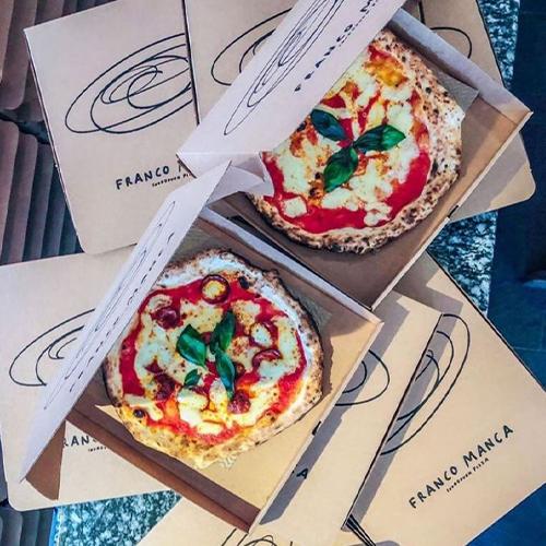 Tomato, mozzarella and basil pizza inside a pizza box from Franco Manca