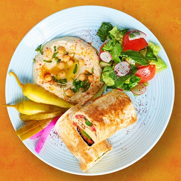 A plate of food from Comptoir Libanais including hummus and a wrap.