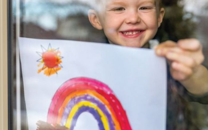 young boy holding up a painting done by a child of a rainbow and the sun
