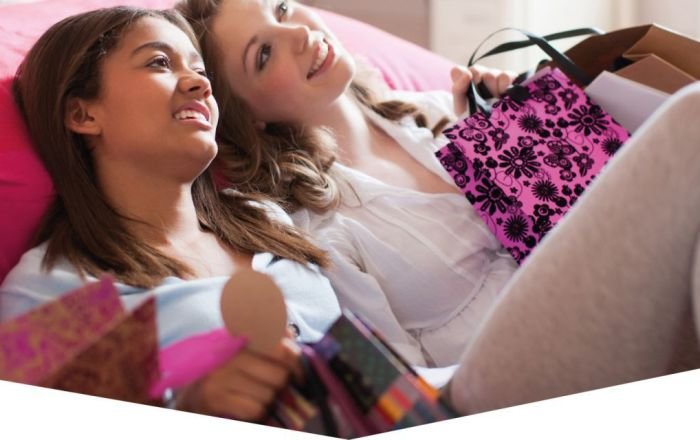Two teenage girls with shopping bags smiling