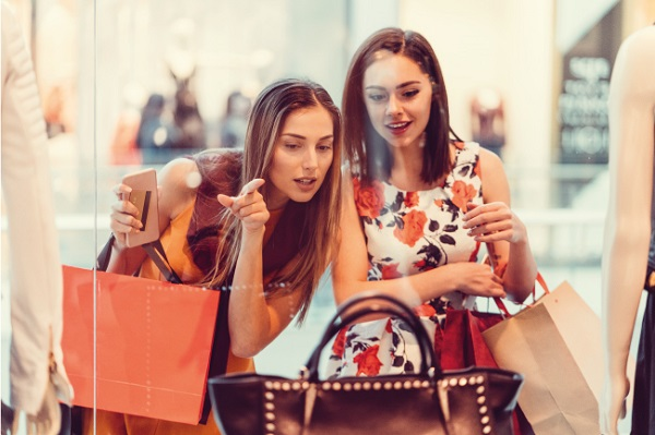 two women looking at a handbag through a shop window