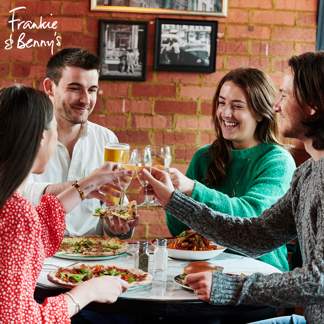 group of people toasting a drink in the air at a table with dishes from Frankie & Benny's on it