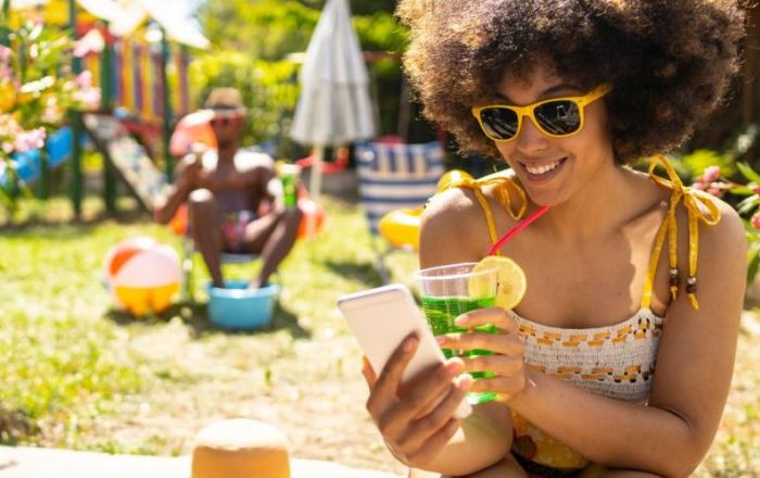 A woman wearing sunglasses and holding a colourful drink and smartphone. There is a sunny garden with a man behind.