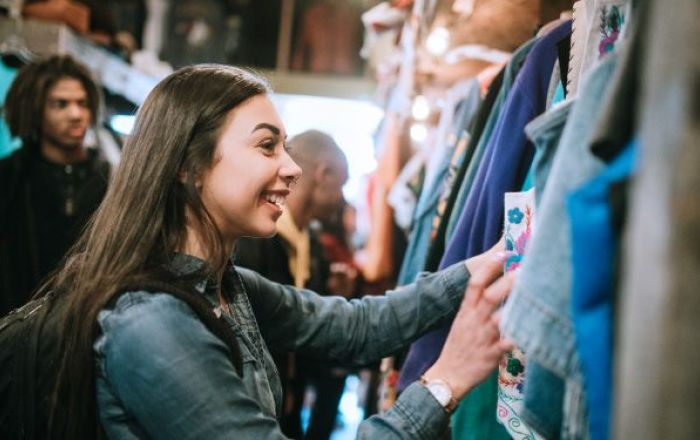 A girl looking at a rack of clothes