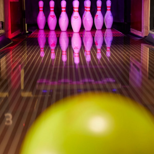 A close up of a yellow bowling ball, behind it there is a bowling lane and ten bowling pins set up at the bottom of the lane.