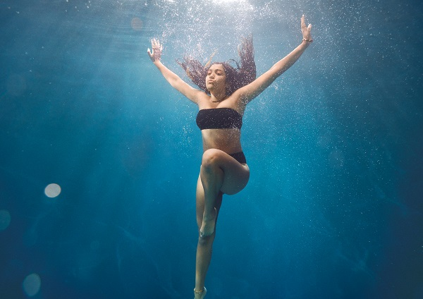 woman underwater in black bikini