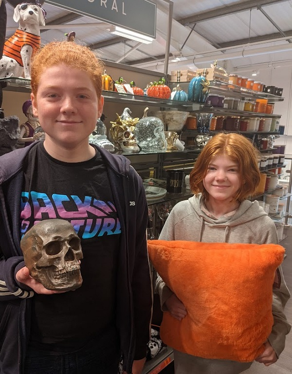 Two young people standing in tk maxx with halloween decor in background.