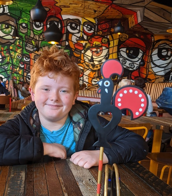 A young person sat at a table in Nandos with a nandos bird table place holder.
