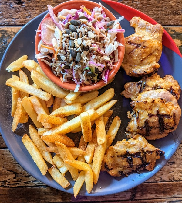 A plate of food with chicken and chips from nandos.