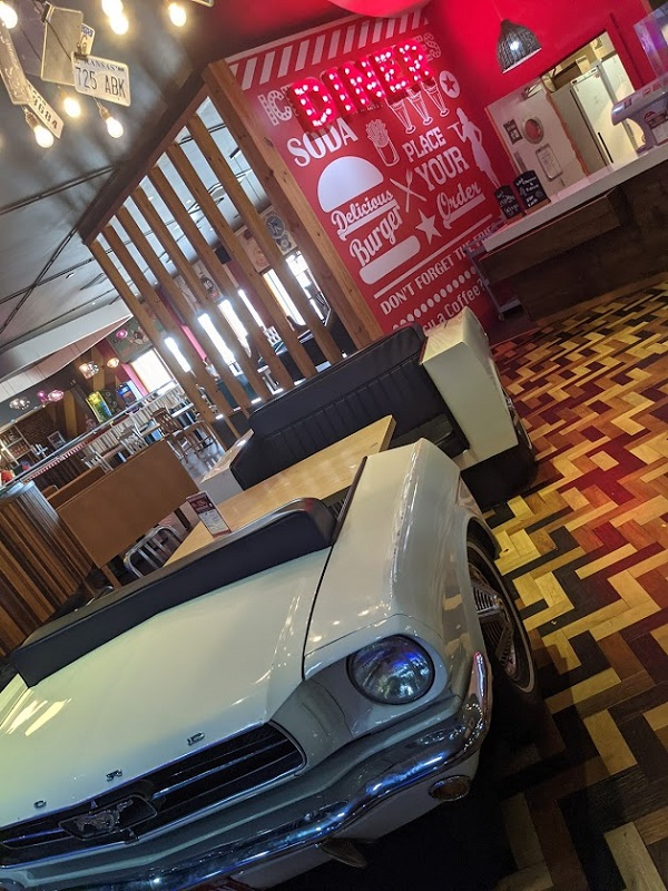 An american style diner table and seats that look like a car.
