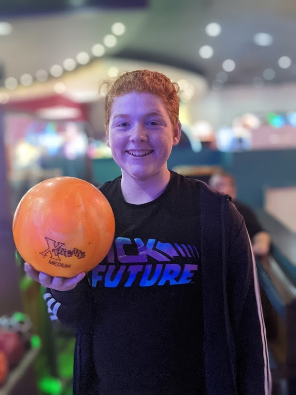 A young person holding an orange bowling ball.