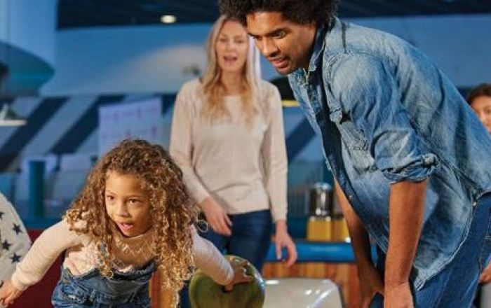 A family playing bowling- the young girl is looking down the lane.