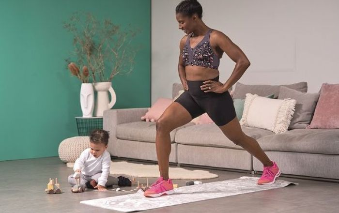 a woman stretching on a yoga mat next to an infant playing.