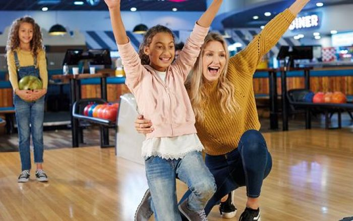 A young girl and a woman playing bowling.