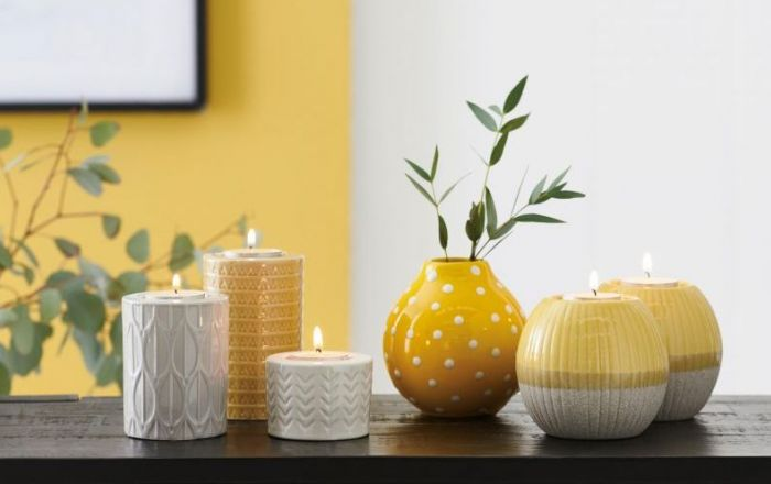 5 yellow and white candles on a table.