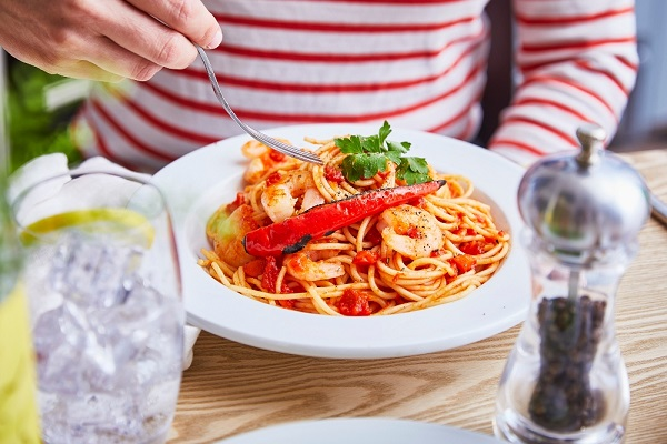 Close up image of pasta with prawns and vegetables.