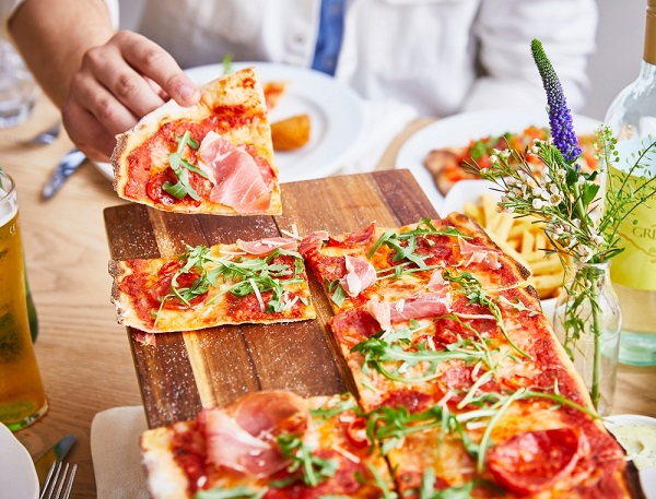 A wooden platter with a pizza cut into slices, a hand is taking one piece.