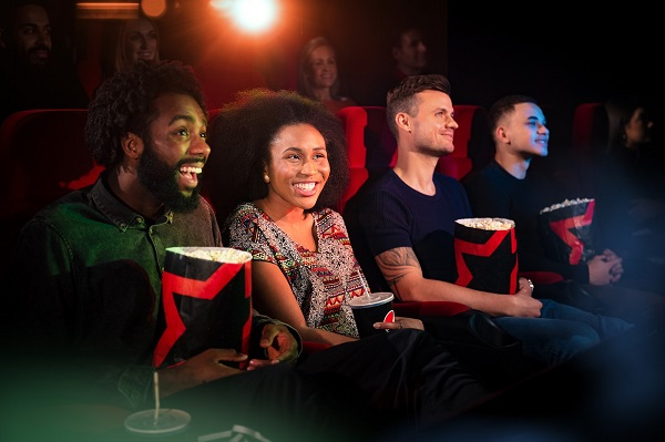 Four people sitting in a cineworld cinema eating popcorn and holding drinks.