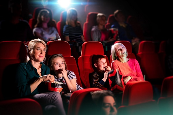 Two adults and two children are sitting in the cinema watching a film whilst eating popcorn.