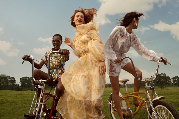 Three women, two riding bikes and one running, they are wearing River Island clothes.