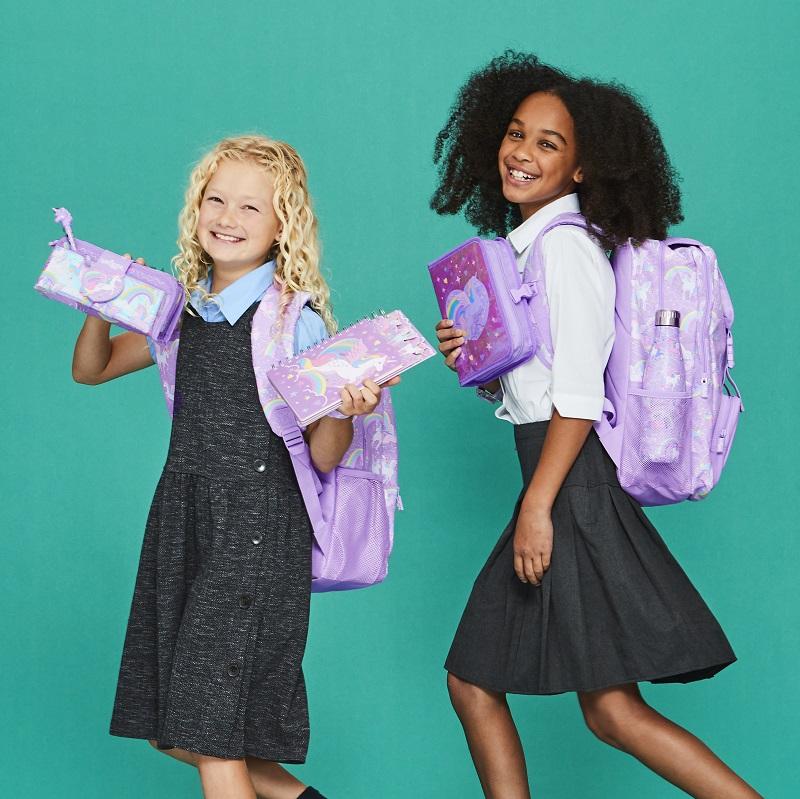Two schoolgirls holding Smiggle stationery.