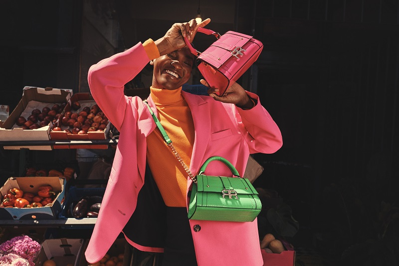 A woman wearing a neon pink jacket and holding a neon pink and neon green purse or handbag.