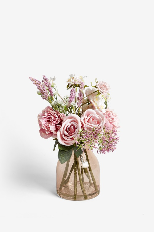 A bouquet of pink flowers in a white vase.