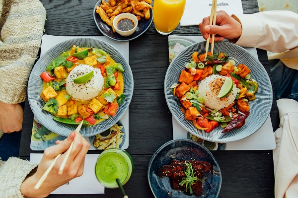 A photo of a table with wagamama food in bowls and the hands of two people eating with chopsticks