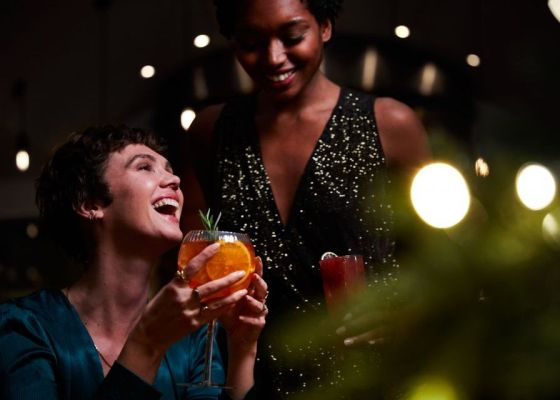 Two women drinking festive cocktails.