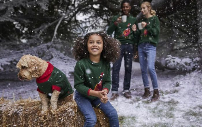 a family and their dog all wearing christmas jumpers from Joules' Woodland Edit with snow falling down in the woods