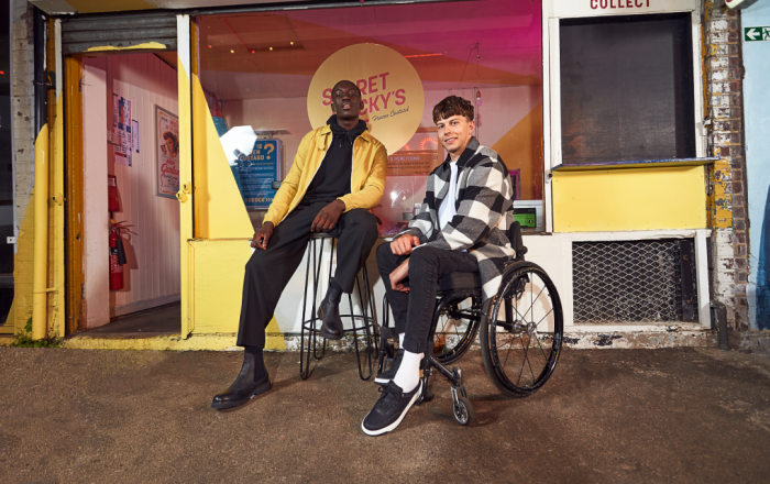 Two people standing outside a shop wearig schuh shoes.
